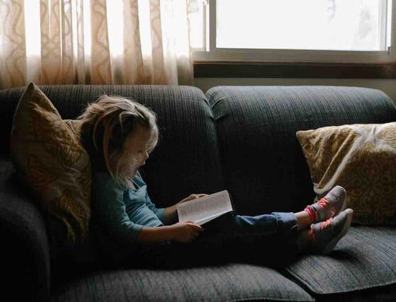 niña_leyendo_en_el_sofa_compromiso_social_susana_requena_560